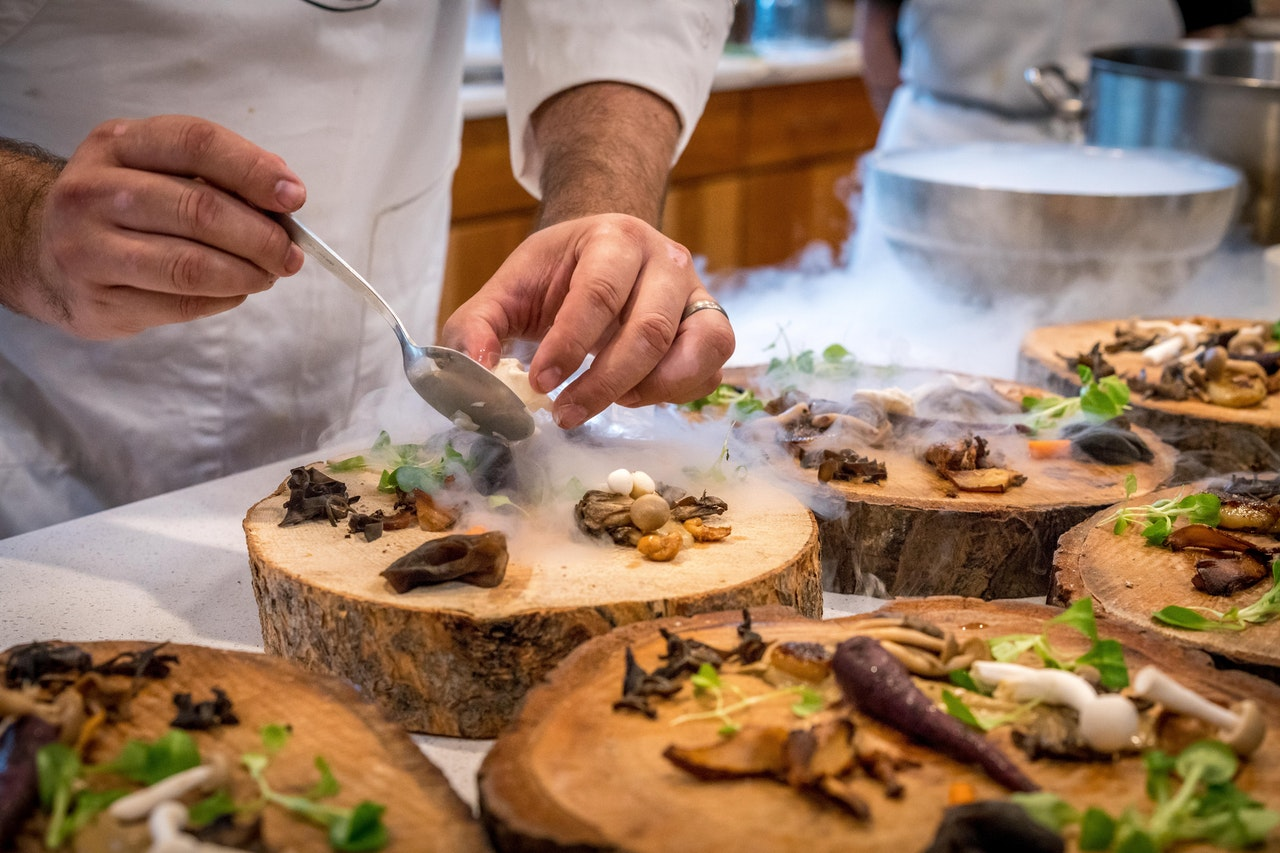 a chef putting fancy food on wooden plates